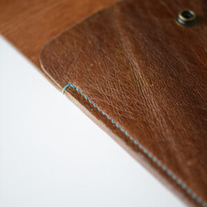 Side view of tan leather laptop case, hand stitched with blue linen thread