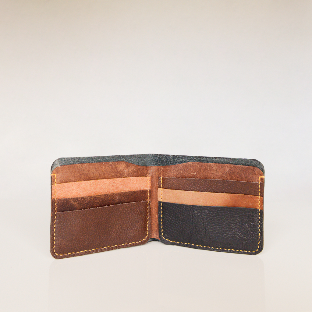 Open view of bifold wallet showing 6 card slots and a compartment for notes. Made from reclaimed and upcycled leather in tan, brown and black