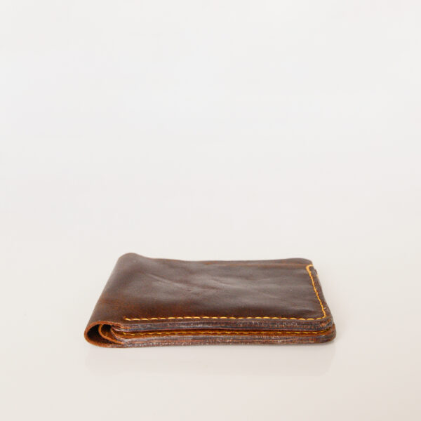 Side view of dark brown leather bifold wallet made from pre-loved leather