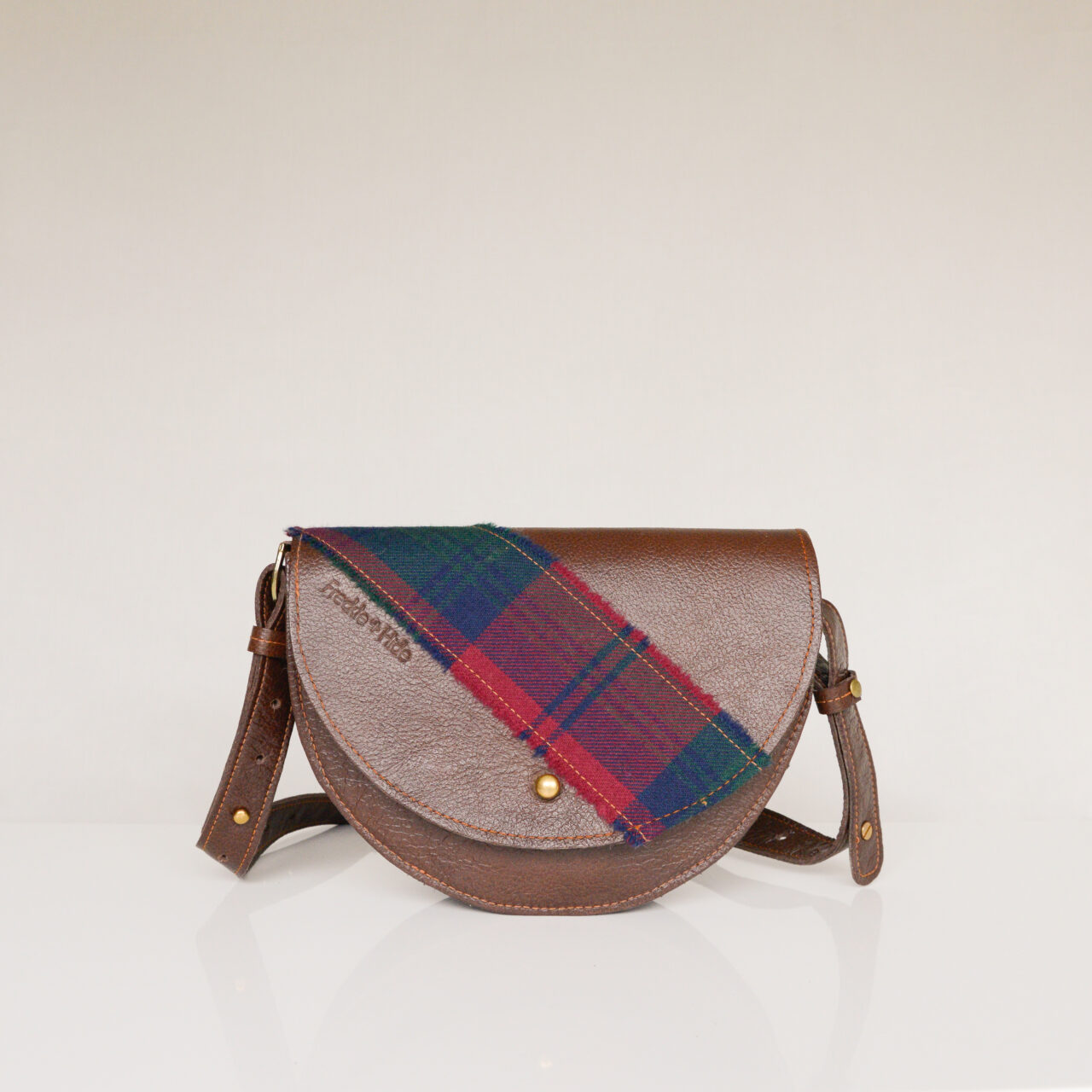 Unique brown bag made from upcycled leather with tartan across flap and on strap