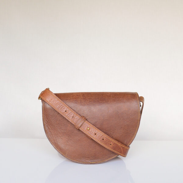 Rear view of luxury tan leather bag with yellow stitching and adjustable shoulder strap.