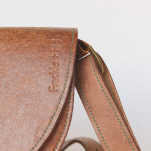 Close up of tan leather shoulder bag showing silver hardware, green stitching and the F+H logo embossed vertically
