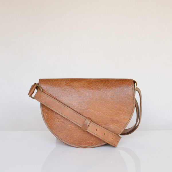 Rear view of rectangular tan leather waist bag made from reclaimed and upcycled leather. Adjustable shoulder strap draped over back of bag