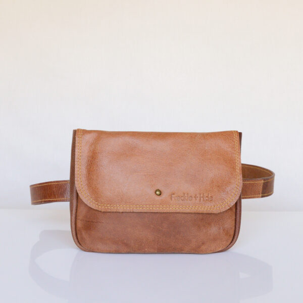 Rectangular tan leather waist bag with flap and stud closure with matching tan leather belt