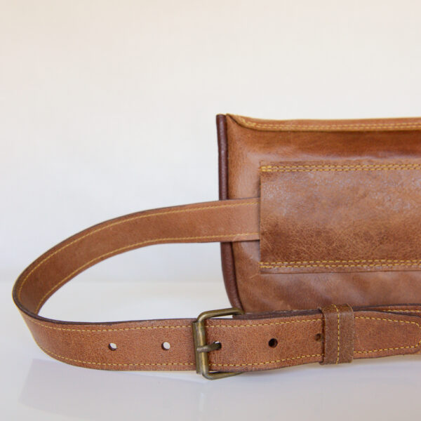 Rear view of tan leather waist bag with matching belt and antique brass belt buckle