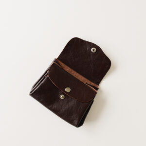 Dark brown leather wallet with silver poppers. Open to show pocket and poppered internal section