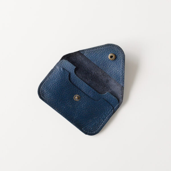 Open view of dark blue leather card wallet showing antique brass popper and 2 slots for cards