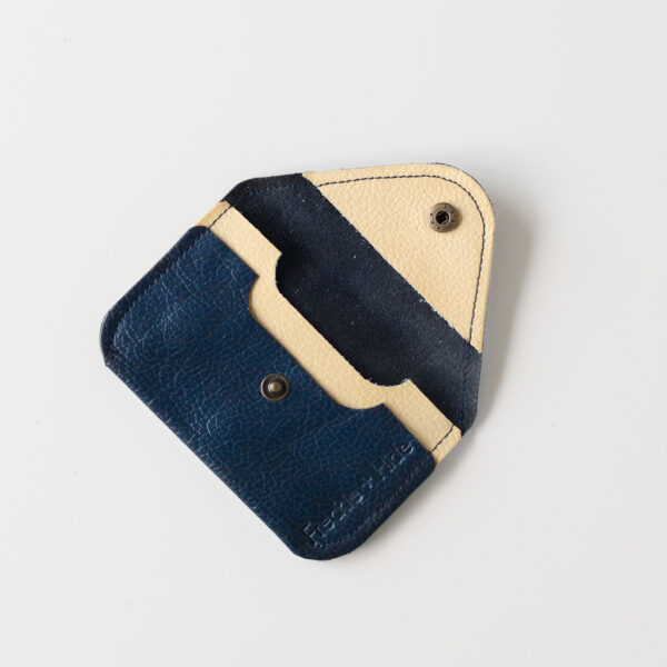 Open view of dark blue leather card wallet with yellow contrast pocket and flap lining. The popper fastening is antique brass and there are 2 card slots