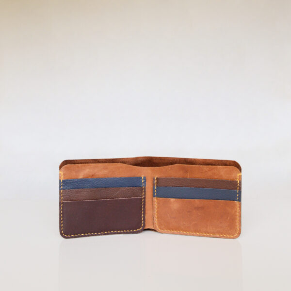 Inside view of leather bifold wallet. Tan, brown and dark blue leather with yellow stitching.