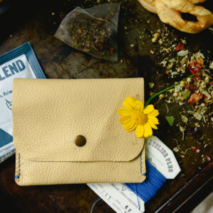 Yellow leather pouch made from reclaimed and recycled leather with black popper closure and stitched with blue linen thread