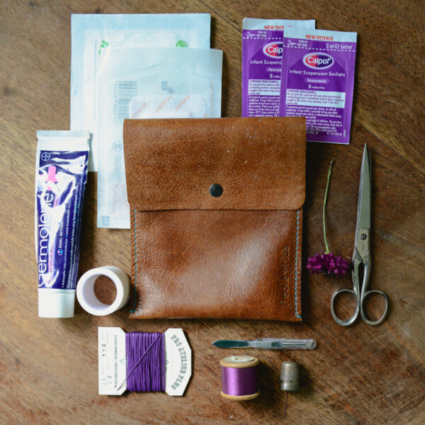 Brown pouch made from reclaimed and recycled leather. Surrounded by first aid supplies
