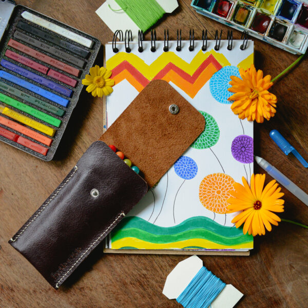 Open brown leather pouch with coloured pens inside surrounded by colourful art materials
