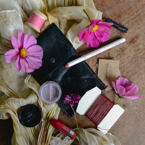 Black recycled leather pouch surrounded by flowers and make up
