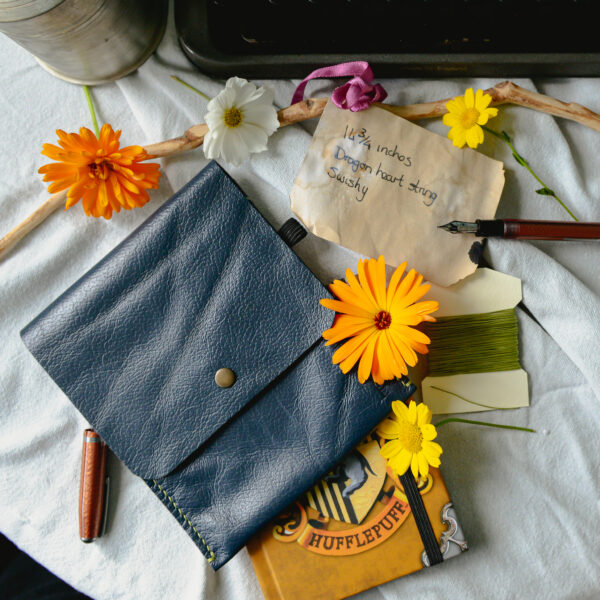 Blue reclaimed leather pouch with notebook and thread surrounded by flowers