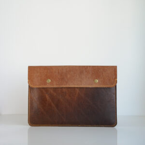 Tan leather laptop case with brass poppers and yellow linen stitching