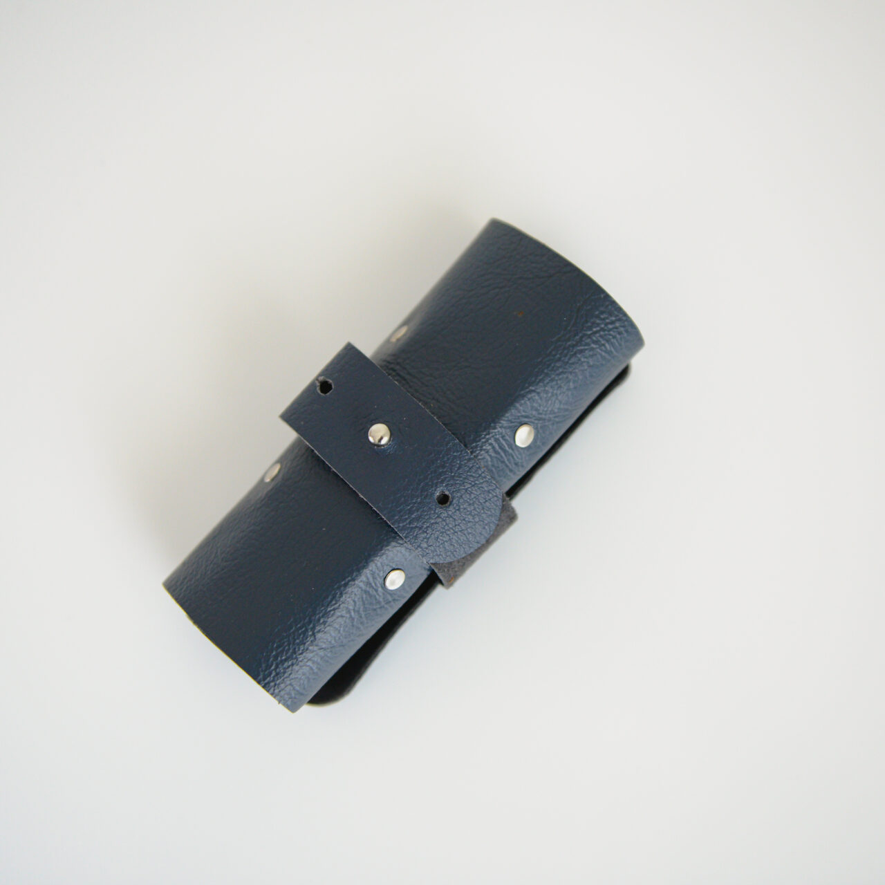 Navy blue rolled up cable tidy with silver rivets
