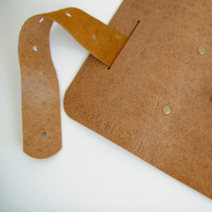 Close up of tan leather cable tidy roll made of recycled leather