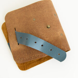 Front of recycled leather cable tidy roll showing antique brass rivets